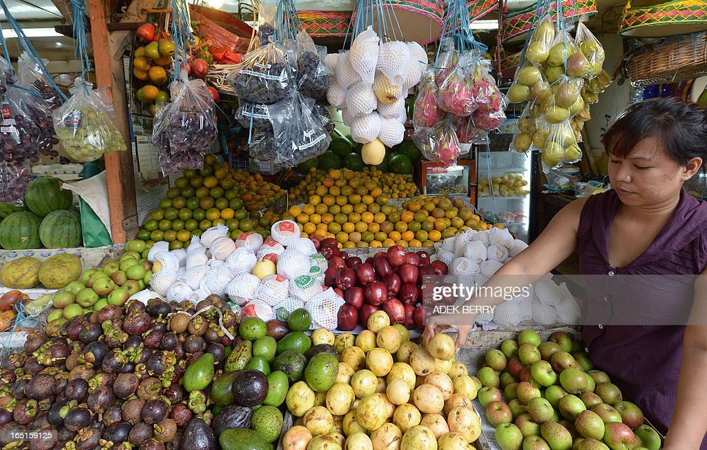 An Indonesian vendor arranges fruits at a traditional market in Jakarta on April 1, 2013. Food ingredients quickened Indonesia's inflation in March to 5.9 percent year-on-year, surpassing the central bank's range target of 5.5 percent, the statistics office said on April 1. Indonesians who love adding lavish spices in their meal saw a steep rise in the prices of shallots, garlic and chili. AFP PHOTO / ADEK BERRY