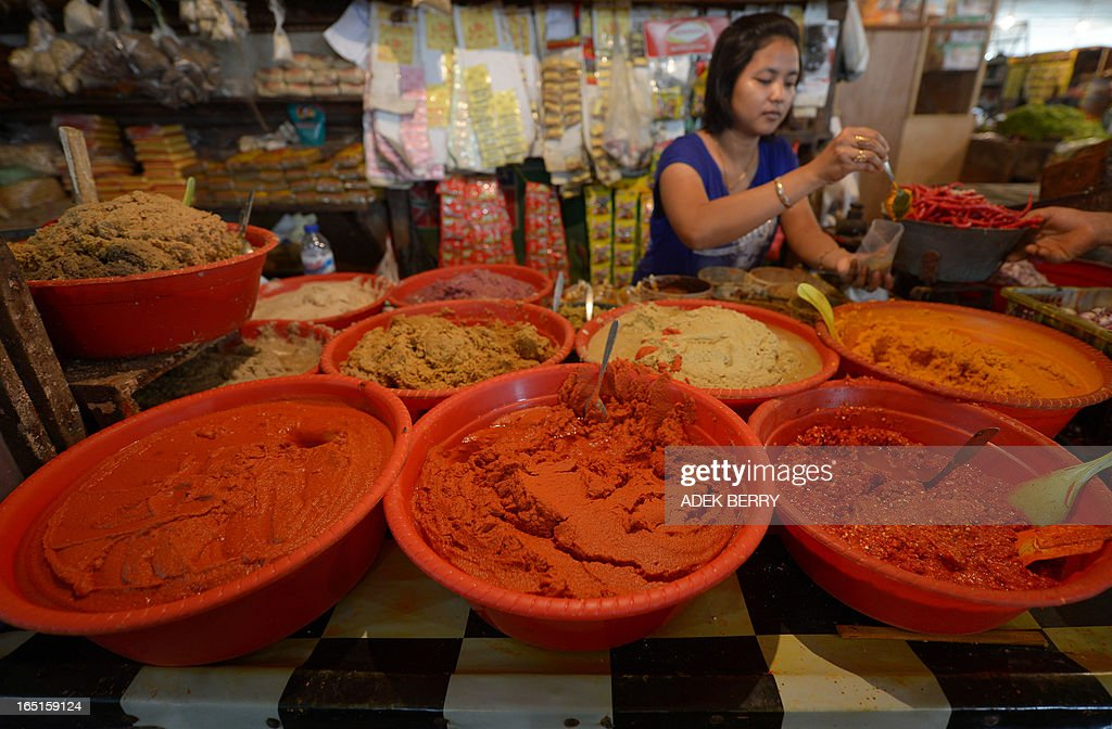 An Indonesian vendor serves a customer at a traditional market in Jakarta on April 1, 2013. Food ingredients quickened Indonesia's inflation in March to 5.9 percent year-on-year, surpassing the central bank's range target of 5.5 percent, the statistics office said on April 1. Indonesians who love adding lavish spices in their meal saw a steep rise in the prices of shallots, garlic and chili.