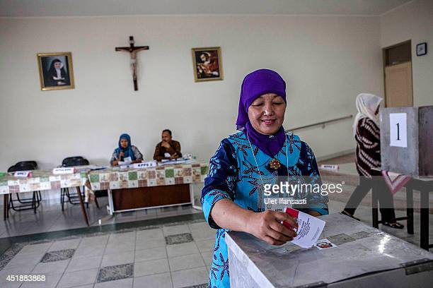 An Indonesian woman casts her ballot at a polling station during the Indonesia presidential election on July 9 2014 in Yogyakarta Indonesia Election...