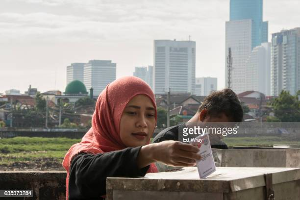 An Indonesian woman casts her ballot in the governor's election at a polling station on February 15 2017 in Jakarta Indonesia Residents of...