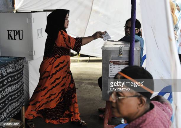 An Indonesian woman casts her vote in local elections at a polling station in Jakarta on February 15 2017 Jakarta's Christian governor who is...