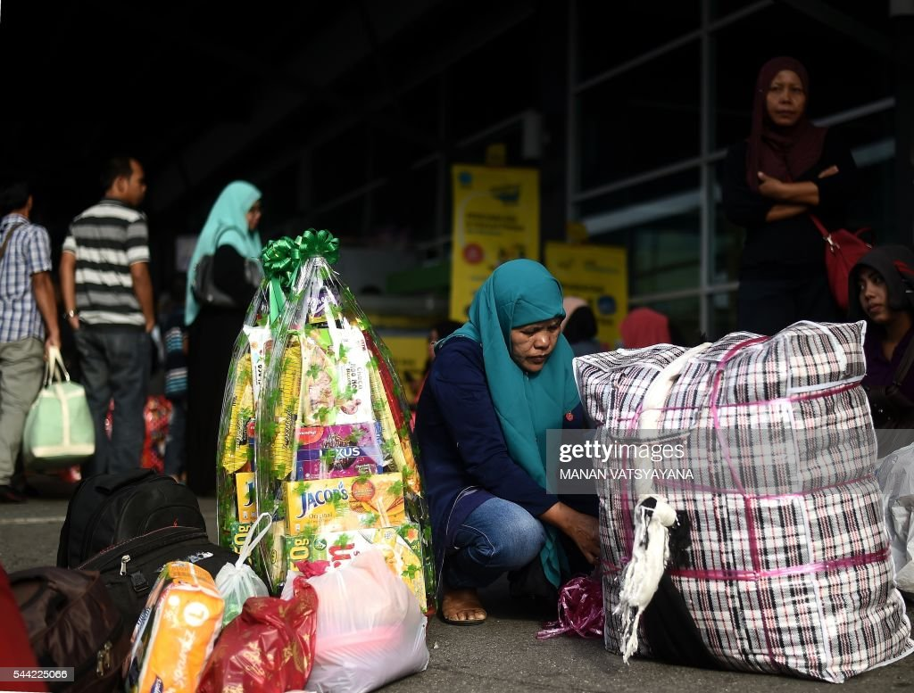 An Indonesian woman does last-minute packing as she waits to board a ferry to head home ahead of the Eid al-Fitr festival at the port passenger terminal in Port Klang on July 2, 2016. A large number of Indonesians living in Malaysia head back home to celebrate Eid Al-fitr festival with their families during the last days of the fasting month of Ramadan. / AFP / MANAN