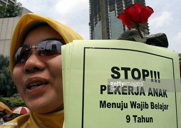 An Indonesian woman holds a poster that reads 'stop child worker' during a May Day rally in Jakarta 01 May 2007 About 1500 protests gathered to mark...