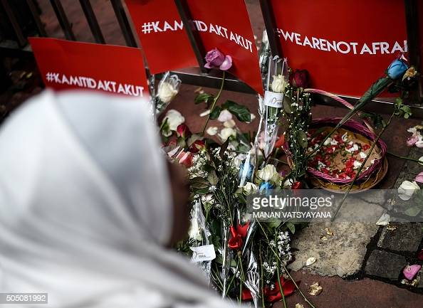 TOPSHOT An Indonesian woman offers flowers during a vigil outside the damaged Starbucks coffee shop in central Jakarta on January 15 a day after a...