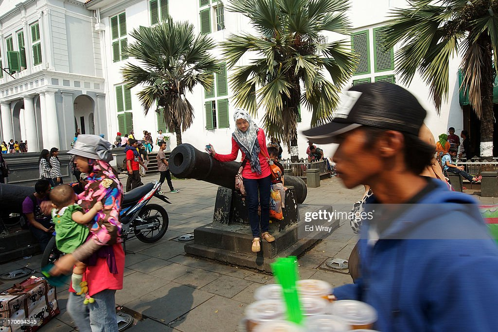 An Indonesian woman poses for her friend on an old canon in front of the former Jakarta Governor's house in Kota Tua Sunday June 16, 2013 in Jakarta, Indonesia. Once known as the 'Queen of the East', Kota Tua, which means Old Town in Indonesian, is the original city of Jakarta built by the Dutch in the 16th century and called Batavia at that time. Currently, Kota Tua's beautiful Colonial architecture is in ruins, abandoned as the city edged farther south over the years. Jakarta's Governor, Joko Widodo, hopes to make it a priority to restore the old town and develop it into a high end tourist destination..