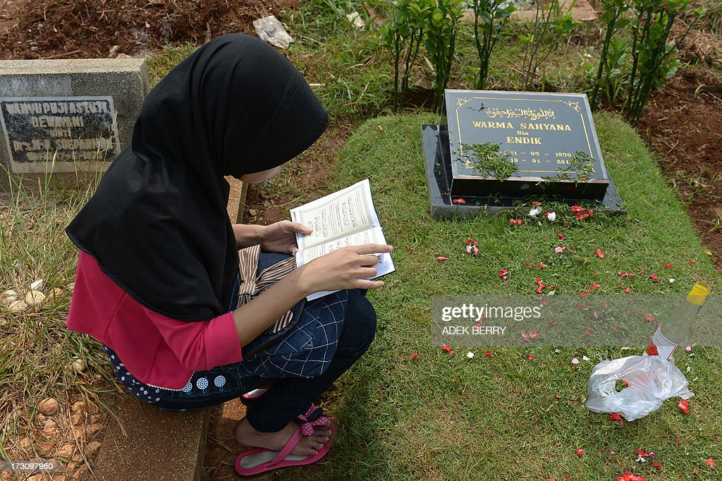 An Indonesian woman reads a copy of a Koran at a cemetary as Muslims in the country follow a tradition of visiting the graves of loved ones ahead of the holy month of ramadan, in Jakarta on July 7, 2013. Ramadan is a holy month celebrated by Muslims worldwide marked by fasting, abstaining from foods, sex and smoking from dawn to dusk for soul cleansing and strengthening the spiritual bond between them and the Almighty.