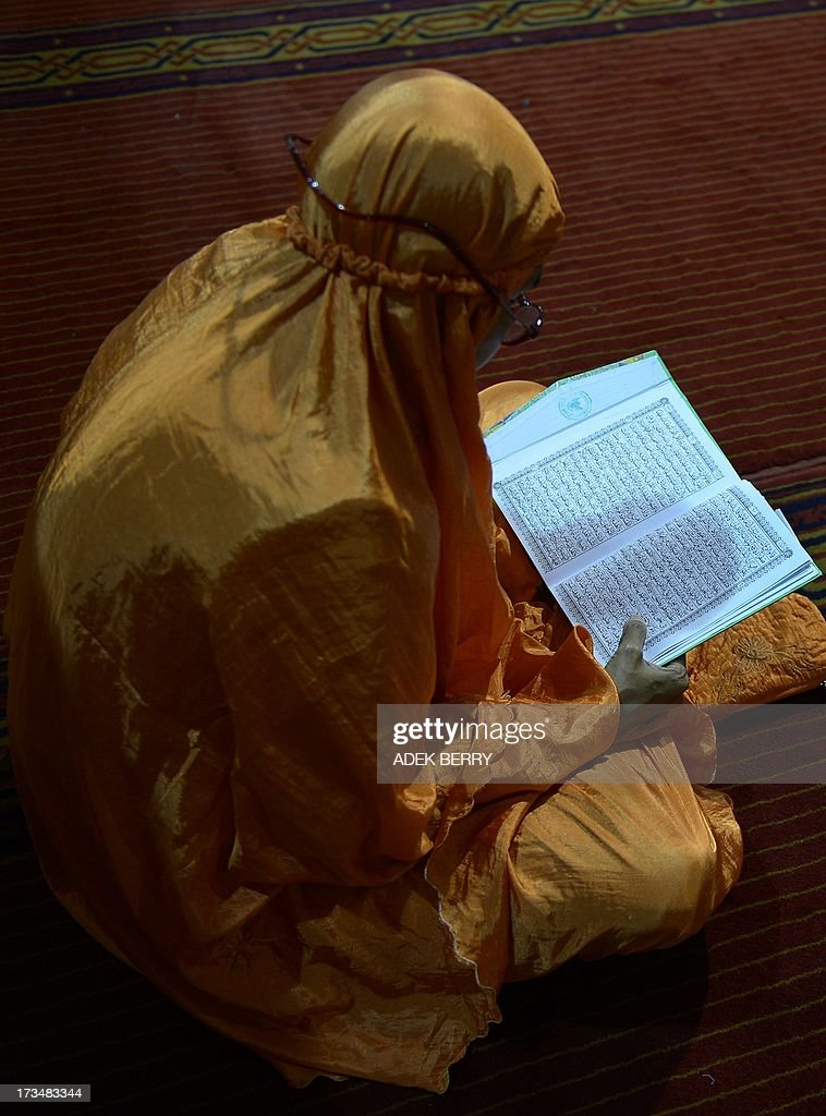 An Indonesian woman reads a copy of the Koran at the Istiqlal mosque on the 6th day of Ramadan in Jakarta on July 15, 2013. Tens of millions across the Muslim world fast from dawn to dusk and strive to be more pious and charitable during the month, which ends with the Eid holiday.