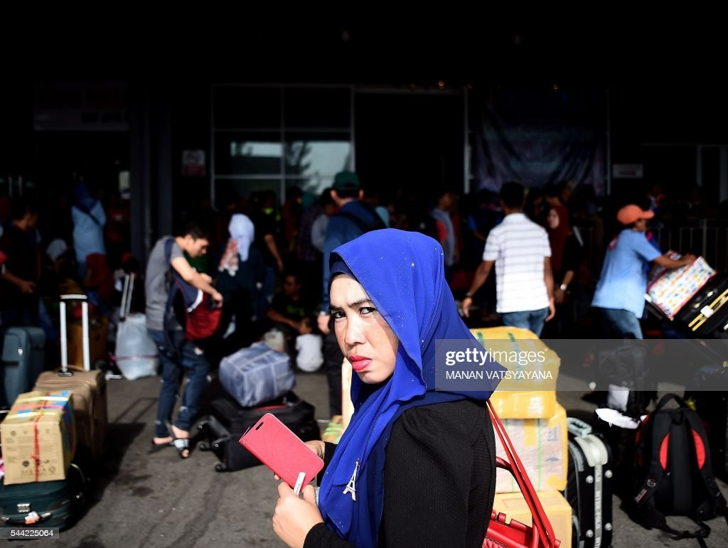 An Indonesian woman Rehma waits to board a ferry to head home ahead of the Eid al-Fitr festival at the port passenger terminal in Port Klang on July 2, 2016. A large number of Indonesians living in Malaysia head back home to celebrate Eid Al-fitr festival with their families during the last days of the fasting month of Ramadan. / AFP / MANAN