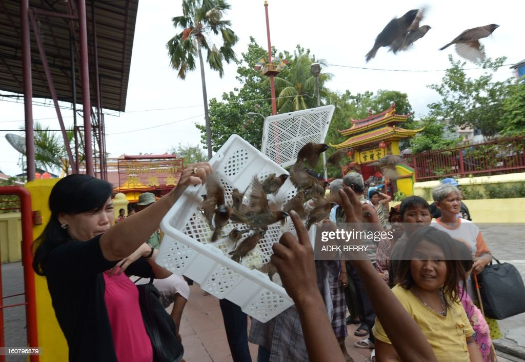 An Indonesian woman (L) releases birds as she gives alms to the needy at the Jin De Yuan Buddhist temple in Jakarta on February 6, 2013, ahead of the Chinese Lunar New Year. The Chinese New Year of the Snake falls on February 10, 2013.