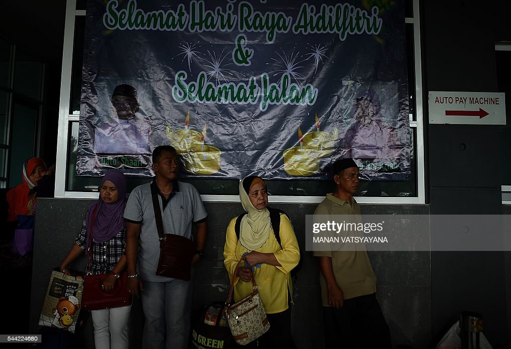 An Indonesian woman Saria (2R) waits in a queue to board a ferry to head home ahead of the Eid al-Fitr festival at the port passenger terminal in Port Klang on July 2, 2016. A large number of Indonesians living in Malaysia head back home to celebrate Eid Al-fitr festival with their families during the last days of the fasting month of Ramadan. / AFP / MANAN