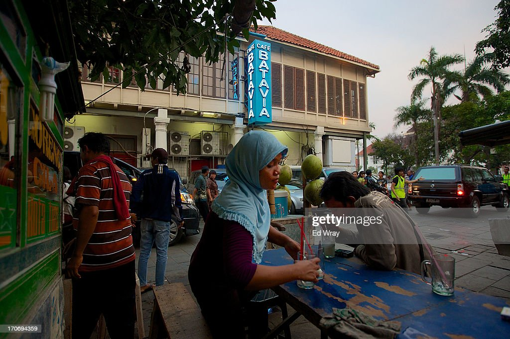 An Indonesian woman selling coconut juice cleans a table at her stall in Kota Tua Sunday June 16, 2013 in Jakarta, Indonesia. Once known as the 'Queen of the East', Kota Tua, which means Old Town in Indonesian, is the original city of Jakarta built by the Dutch in the 16th century and called Batavia at that time. Currently, Kota Tua's beautiful Colonial architecture is in ruins, abandoned as the city edged farther south over the years. Jakarta's Governor, Joko Widodo, hopes to make it a priority to restore the old town and develop it into a high end tourist destination..