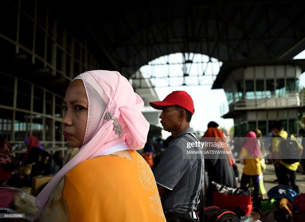 An Indonesian woman wearing an embroidered 'tuding' or headscarf waits to board a ferry to head home ahead of the Eid al-Fitr festival at the port passenger terminal in Port Klang on July 2, 2016. A large number of Indonesians living in Malaysia head back home to celebrate Eid Al-fitr festival with their families during the last days of the fasting month of Ramadan. / AFP / MANAN