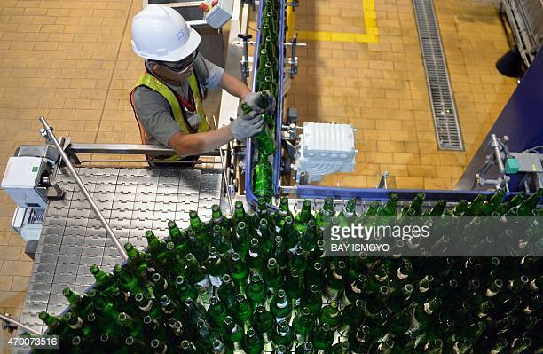 An Indonesian worker monitors a machine at the Multi Bintang Indonesia beer factory and bottling facility in Tangerang in Banten province on April 17...