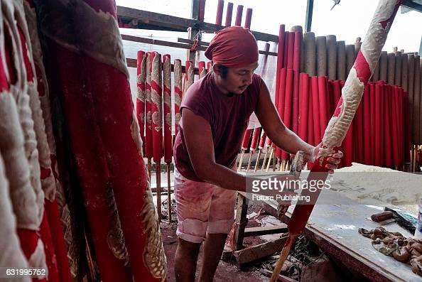 An Indonesian worker seen processing incense sticks at a local factory ahead of Chinese Lunar new year's day celebrations on January 16 2017 in North...