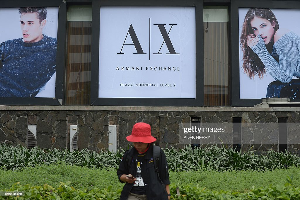 An Indonesian worker sits before luxury brand advertising as workers rally in Jakarta on November 22, 2012. Thousands workers took to the street demanding Indonesia's government to increase their wages, to improve working condition and end the practice of outsourcing manpower.