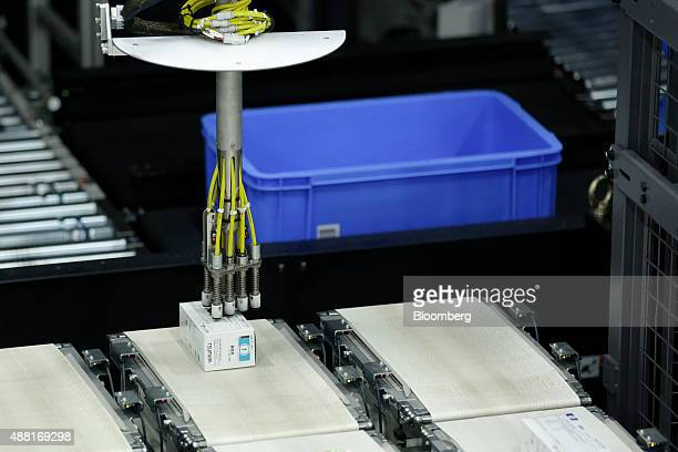 An industrial robot manufactured by Yaskawa Electric Corp places a box of pharmaceutical product onto a conveyor belt at a Toho Pharmaceutical Co...