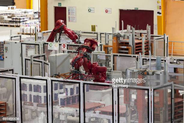 An industrial robot stacks buckets of paint on pallets at an Akzo Nobel India Ltd paint factory in Gwalior Madhya Pradesh India on Thursday June 1...
