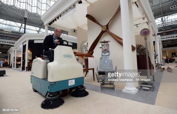 An industrial vacuum cleaner makes its way past stands as last minute preparations are made at the Olympia International Art Antiques Fair which runs...