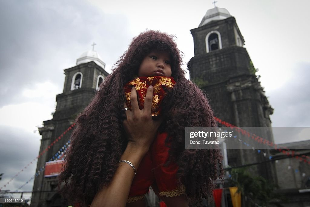An infant dressed as the Child Jesus is hoisted in the air during the feast of the Santo Nino in the working class district of Tondo on January 19, 2013 in Manila, Philippines. The annual Catholic celebration signals the start of festivities in various parts of the Philippines.