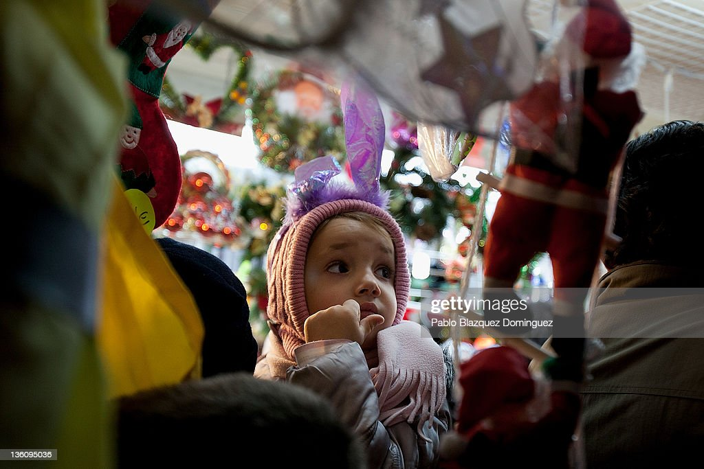 An infant watches christmas toys at a shop in a Christmas market fair at Plaza Mayor Square six days before Christmas Day on December 19, 2011 in Madrid, Spain. This year businesses are starting sales and discounts before Christmas to try and gain customers during the current economic crisis.