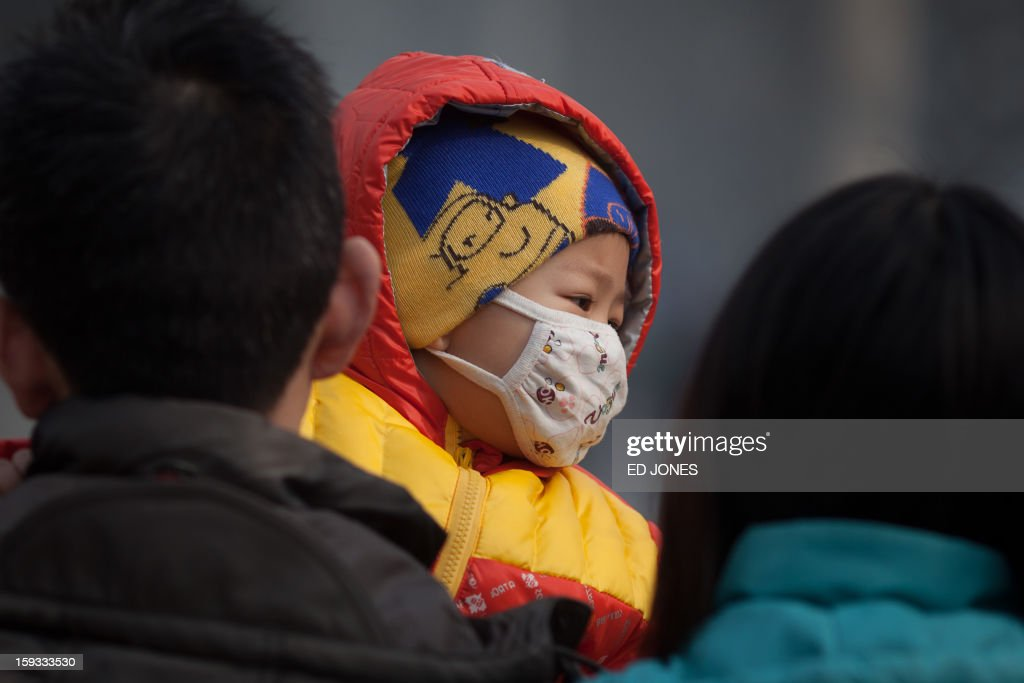 An infant wearing a mask (C) is carried along a street in severe pollution in Beijing on January 12, 2013. Air quality data released via the US embassy twitter feed recorded air quality index levels so hazardous that they were classed as 'Beyond Index'. Just after midday the particle matter (PM) 2.5 figure was 519 on a scale that stops at 500, and advises against all outdoor activity. AFP PHOTO / Ed Jones