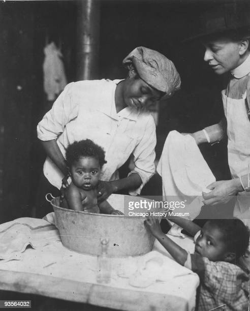 An Infant Welfare Society nurse assists an AfricanAmerican mother bathing her child Chicago IL 1915 Another child is visible on the lower right...