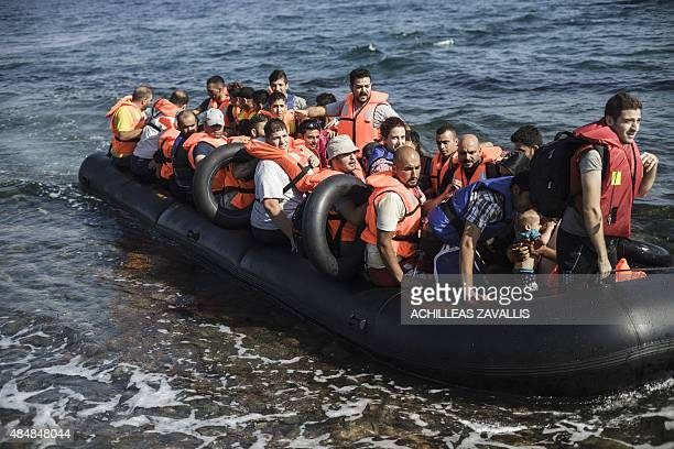 An inflatable boat with Syrian migrants approaches the coast of Lesbos island after crossing the Aegean sea from Turkey on August 22 2015 Turkish...