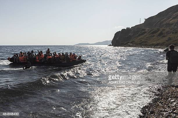 An inflatable boat with Syrian refugees approaches the coast of Lesbos island after crossing the Aegean sea from Turkey on August 22 2015 Turkish...