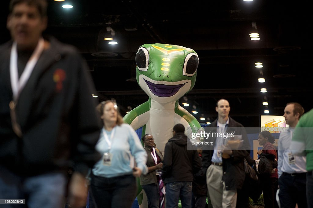 An inflatable Geico gecco mascot stands over Berkshire Hathaway Inc. shareholders as they tour the exhibition floor during the Berkshire shareholders meeting in Omaha, Nebraska, U.S., on Saturday, May 4, 2013. Warren Buffett's Berkshire Hathaway Inc.'s cash hoard hit a record as first-quarter profit jumped 51 percent on gains from equity-linked derivatives and insurance operations. Photographer: Daniel Acker/Bloomberg via Getty Images