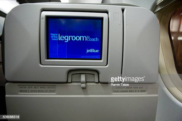 An inflight TV monitor is attached to the seat back aboard JetBlue Airways advertising more legroom in coach than any other airline