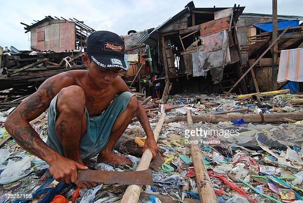 An informal settler prepares materials for a house on the coastal community of Navotas town on October 6 2011 in Manila Philippines The rebuilding of...