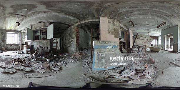 An information poster in Russian stands among debris in the crumbling former hospital on April 9 2016 in Pripyat Ukraine Pripyat built in the 1970s...