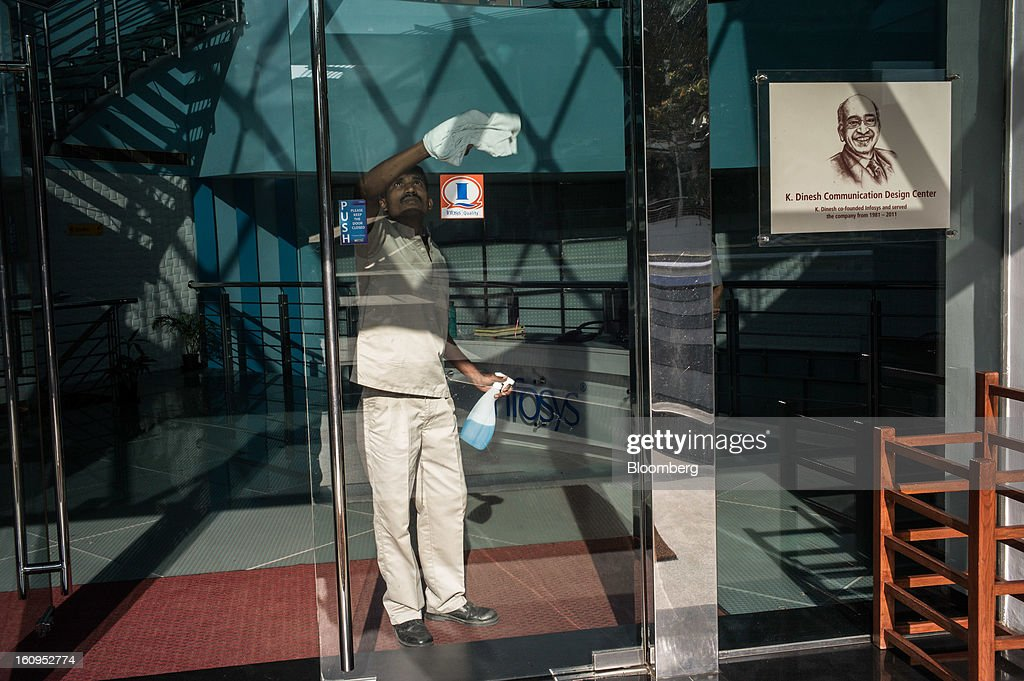 An Infosys Ltd. employee cleans the glass door of the K. Dinesh Communication Design Center at the company's campus in Electronics City in Bangalore, India, on Monday, Feb. 4, 2013. Infosys is India's No. 2 software exporter. Photographer: Sanjit Das/Bloomberg via Getty Images