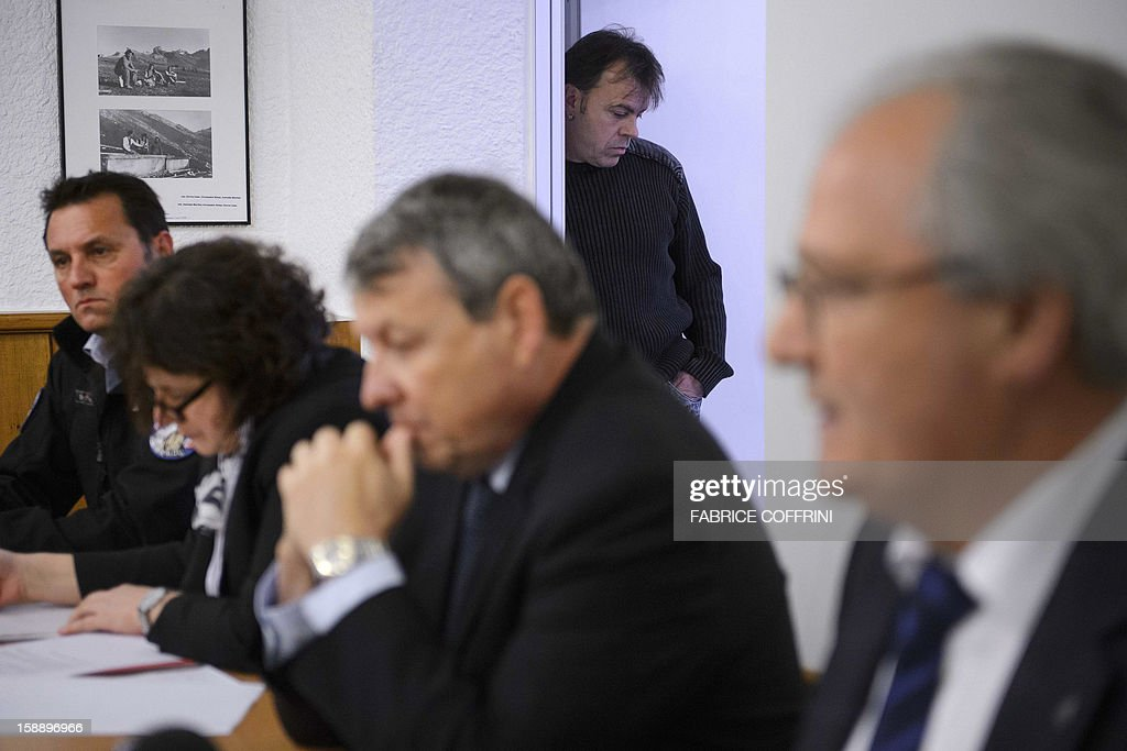 An inhabitant of Daillon listens as he stands in the background while justice Prosecutor Jean-Pierre Gross (C) pauses between prosecutor Catherine Seppey (L) and head of the police Robert Steiner (R) during a press conference on January 3, 2013 in Daillon. A gunman has opened fire in a village in southern Switzerland, killing three people and wounding two others.