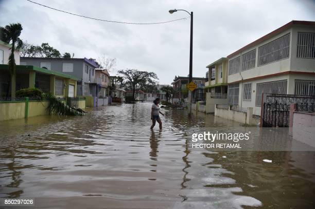 TOPSHOT An Inhabitant of the Puerto Nuevo neighborhood walks through flood water during the passage of Hurricane Maria in the neightborhood Puerto...