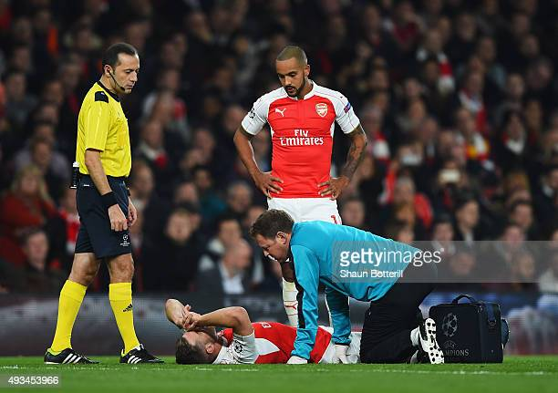 An injured Aaron Ramsey of Arsenal is given treatment as Theo Walcott and referee Cuneyt Cakir look on during the UEFA Champions League Group F match...