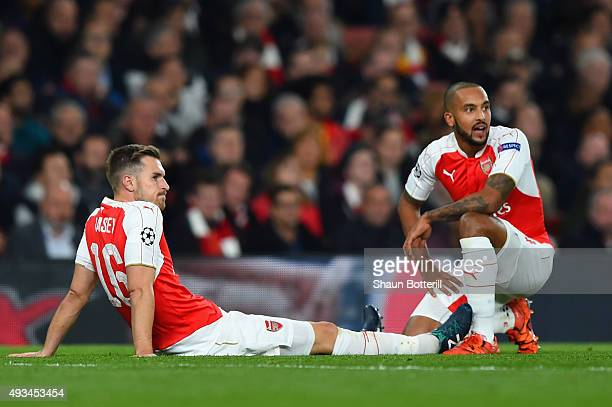 An injured Aaron Ramsey of Arsenal looks on with team mate Theo Walcott during the UEFA Champions League Group F match between Arsenal FC and FC...