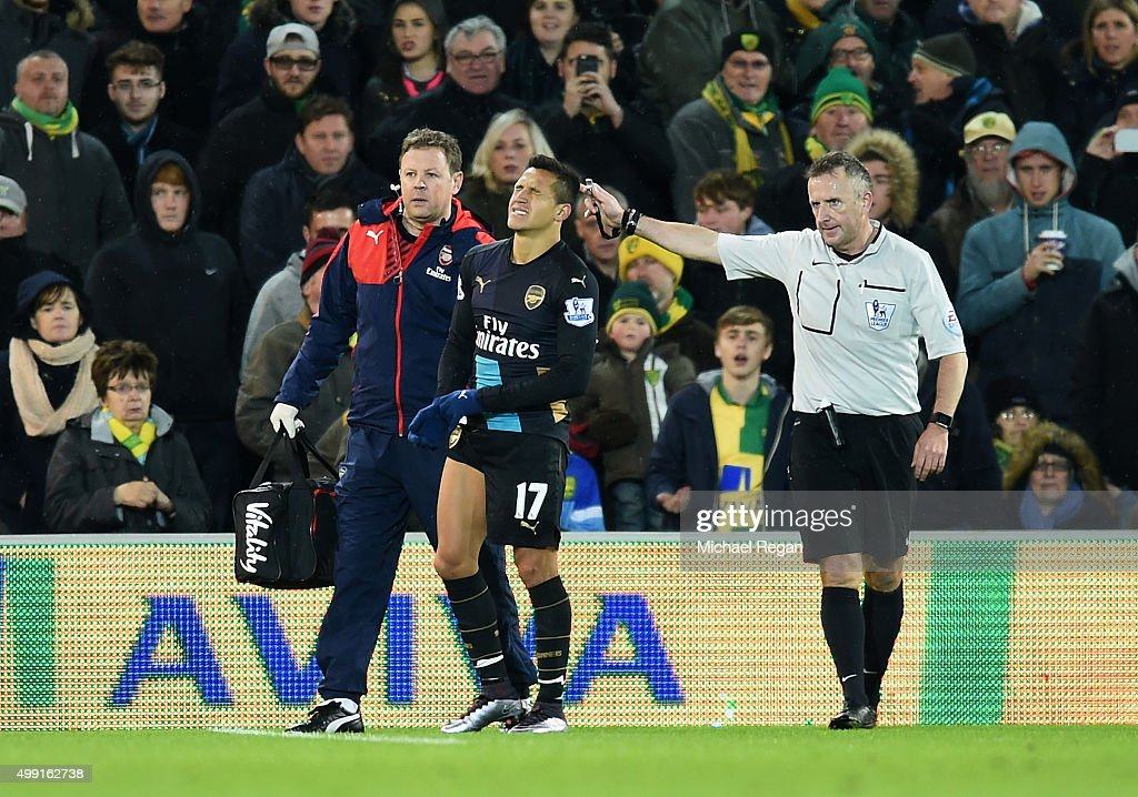 An injured Alexis Sanchez of Arsenal is given assistance during the Barclays Premier League match between Norwich City and Arsenal at Carrow Road on...