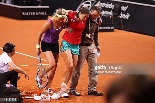 An injured Andrea Petkovic of Germany is taken off the court with the help of opponent Victoria Azarenka of Belarus during day four of the WTA...