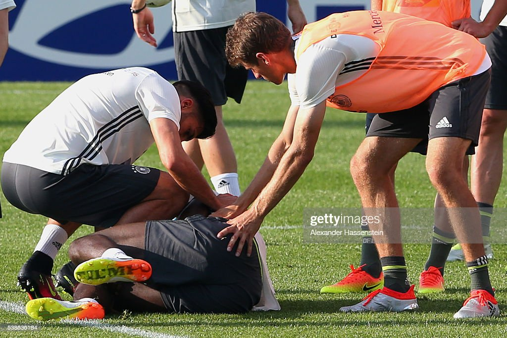 An injured Antonio Ruediger (grounded) is given assistance by his team mate Emre Can (L) and Thomas Mueller (R) during a Germany training session ahead of the UEFA EURO 2016 at Ermitage Evian on June 7, 2016 in Evian-les-Bains, France. Germany's opening match at the European Championship is against Ukraine on June 12.