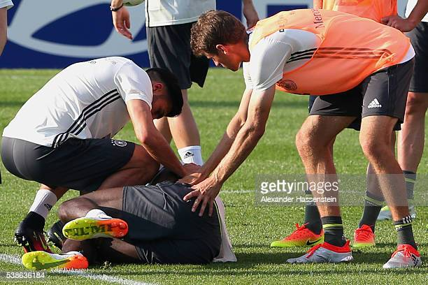 An injured Antonio Ruediger is given assistance by his team mate Emre Can and Thomas Mueller during a Germany training session ahead of the UEFA EURO...