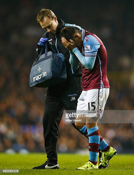 An injured Ashley Westwood of Aston Villa holds his face as he is given assistance during the Barclays Premier League match between Tottenham Hotspur...