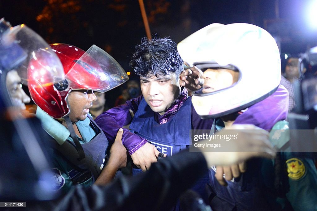 An injured Bangladeshi policeman being assisted after a granade attack at a restaurant nearby in the early hours of July 2 2016 in Dhaka Bangladesh...