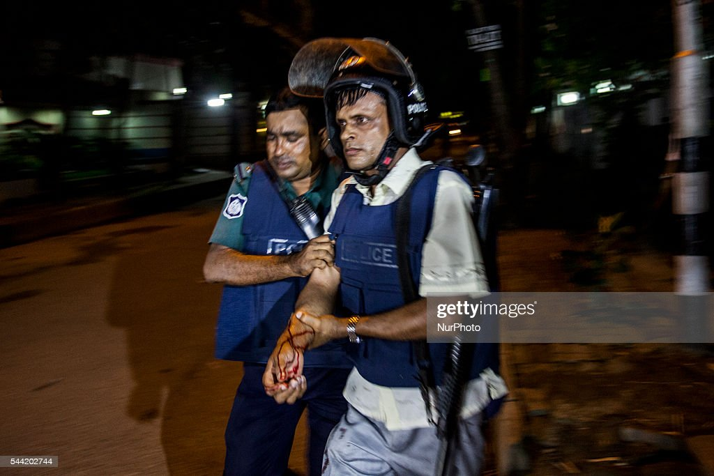 An injured Bangladeshi policeman being assisted after a granade attack at a restaurant nearby in the early hours of July 2, 2016 in Dhaka, Bangladesh. Gunmen have taken at least 20 foreigners hostage at a restaurant in the diplomatic area of Dhaka, the capital of Bangladesh. So-called Islamic State have claimed reponsibility for the attack, which has reportedly left at least 2 police officers dead and many more people injured.