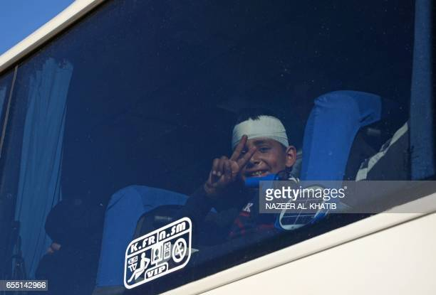 An injured boy flashes the sign for victory as Syrians who were evacuated from Waer the last oppositionheld district of Homs arrive in the northern...