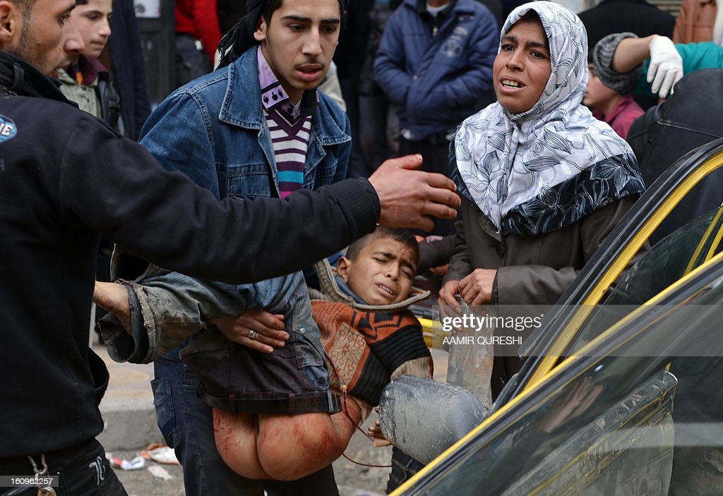 An injured boy is carried out of a taxi as he arrives with his mother at a hospital in the northern city of Aleppo on February 8, 2013, following shelling by government forces. Loyalists troops made ground in the country's north, retaking Karnaz on the strategic Damascus-Aleppo highway on Wednesday after a 16-day onslaught, said Rami Abdel Rahman, head of the Syrian Observatory for Human Rights.