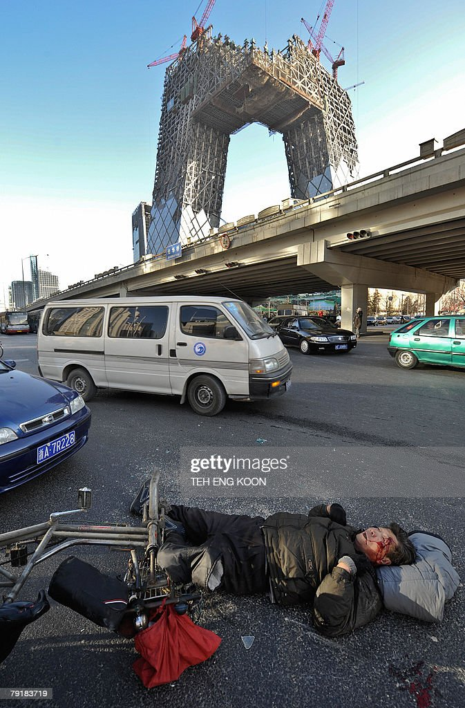 An injured Chinese man lies on a road in front of the under construction China Central Television (CCTV) tower at the Central Business District (CBD) in Beijing, 24 January 2008 after he was hit by a vehicle. Industrial and road accidents killed 101,480 people in China last year, a drop of about 10 percent compared to 2006, the state's safety watchdog said in a report seen 13 January as most fatalities occurred on China's dangerous roads, although there were fewer traffic deaths in 2007 than in 2006.