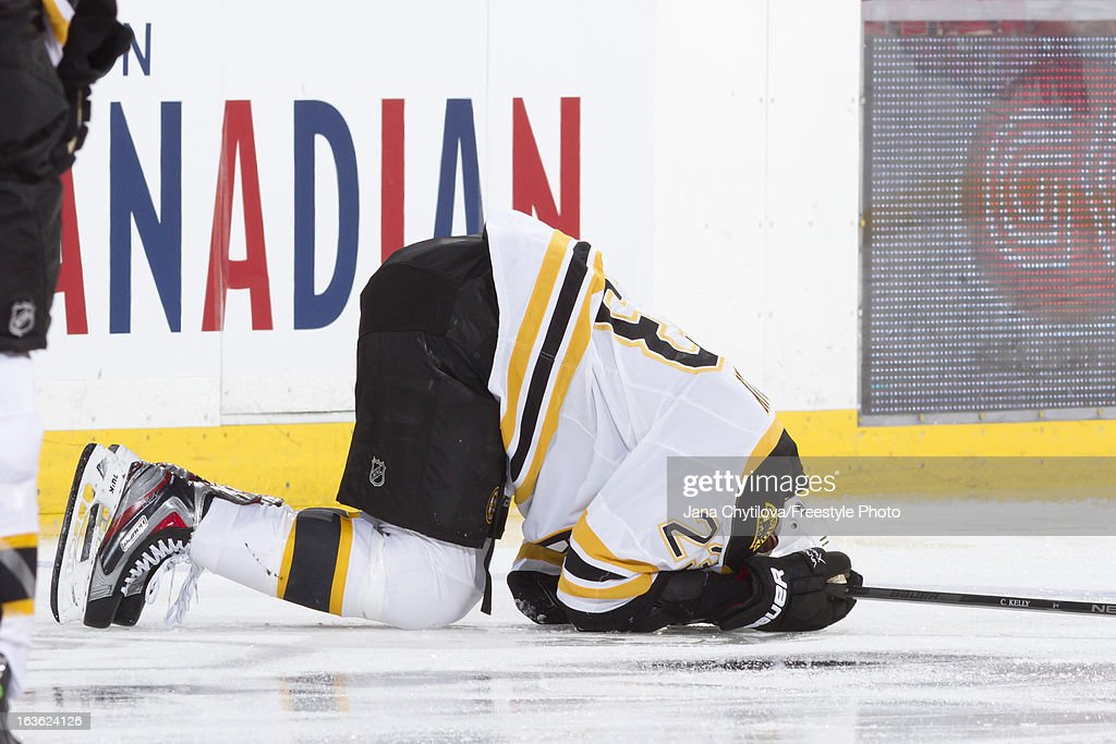 An injured Chris Kelly of the Boston Bruins lies on the ice after a check during an NHL game against the Ottawa Senators at Scotiabank Place on March...
