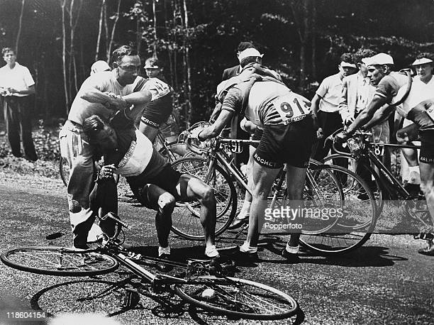 An injured competitor is helped to his feet after a fall during a stage on the Tour de France 1952