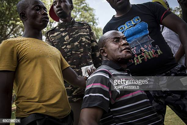 An injured Congolese protester stands after police open fire wth rubber bullets whilst they protest outside the Democratic Republic of the Congo's...